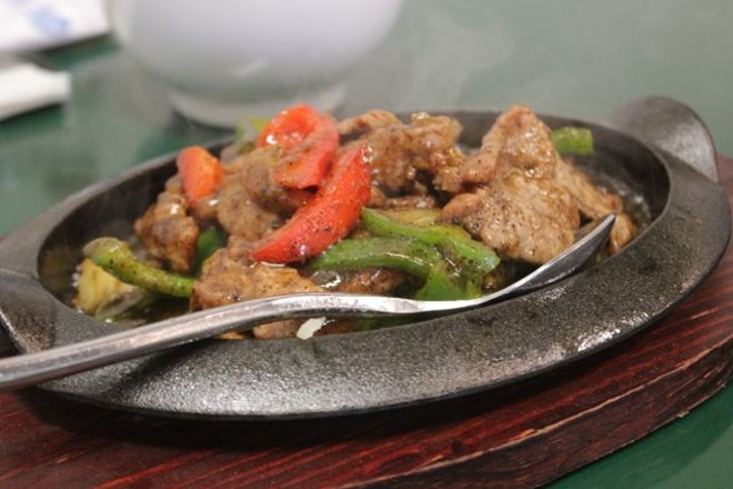 The sizzling beef lives up its name — served in a pan hot from the oven. - PHOTO BY SARAH FENSKE