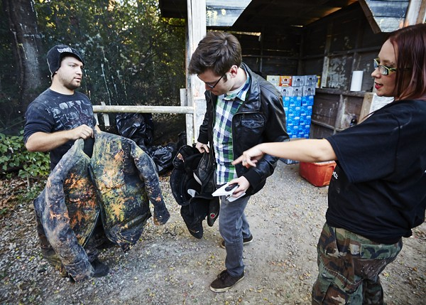 Chelsie Kurschinske, right, describes how a padded vest and hockey pants will protect me from paintball assault.