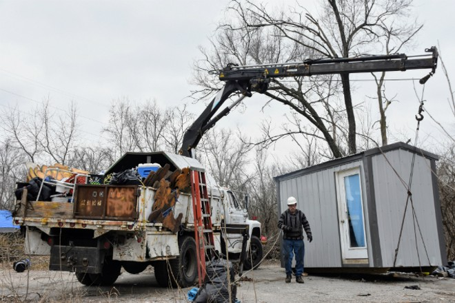 Phil Berwick prepares a hut at an East St. Louis homeless camp for moving. - DOYLE MURPHY