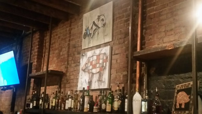 The bar at The Copper Pig has a stylish feel — and some good pig art. - PHOTO BY KATIE INEICH