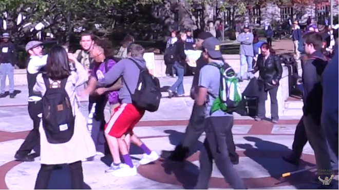 Jesse Morrell (far left, in cap) being confronted by a young man in a purple T-shirt.