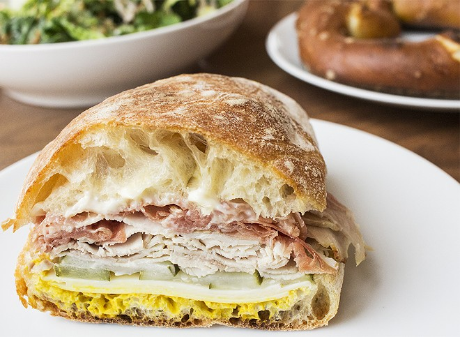 The roasted pork sandwich comes with country ham, gruyere, pickles, mustard and garlic mayonnaise on ciabatta. - MABEL SUEN