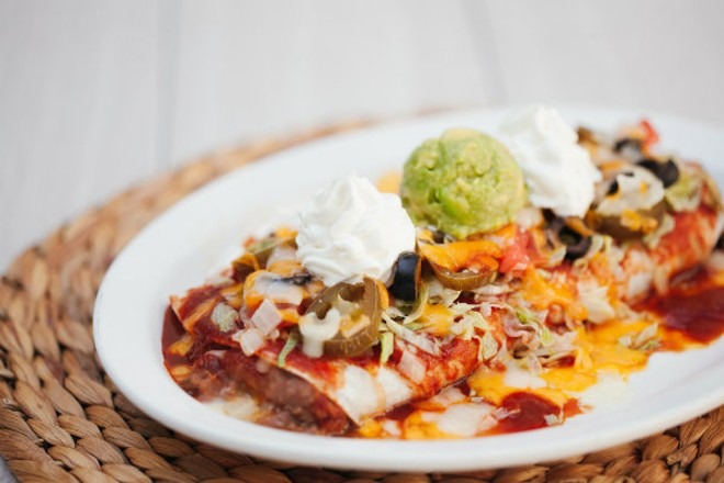 "Hacienda's signature ""wet burrito"" comes smothered in cheesy sauce. - PHOTO COURTESY OF HACIENDA"