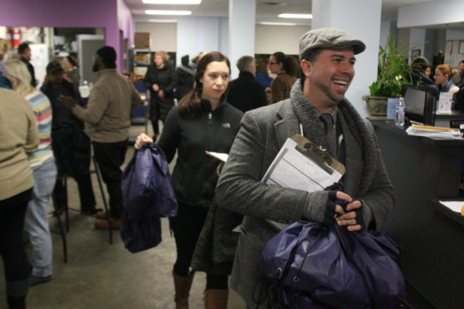 Nelson Perez (right) and Kara Born carry gift bags for the homeless out of Places for People shortly after 4 a.m. on Tuesday. - PHOTO BY DOYLE MURPHY