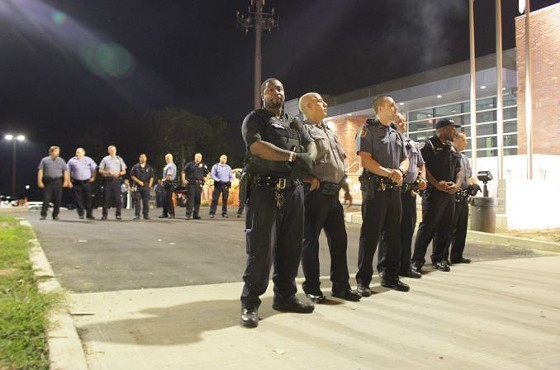 Officers stand guard over the Ferguson Police Department in September 2014 - DANNY WICENTOWSKI