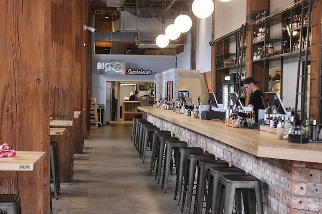 Reclaimed brick form the base of the custom bar, which runs 85 feet. - SARAH FENSKE
