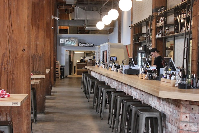 Reclaimed brick form the base of the custom bar, which runs 85 feet. - SARAH FENSKE