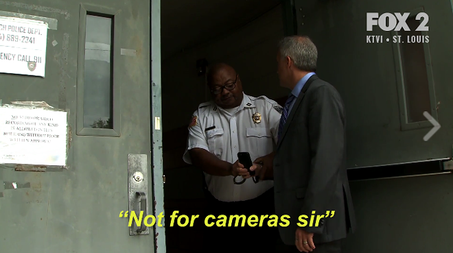 A Kinloch police captain handcuffs Fox 2 reporter Chris Hayes at the doorway of a city meeting. - IMAGE VIA FOX 2
