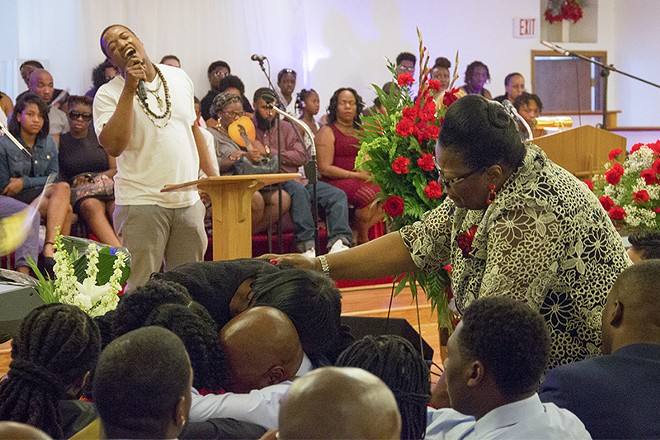 Family members of Edward Crawford embrace during his funeral on May 15, 2017. - DANNY WICENTOWSKI