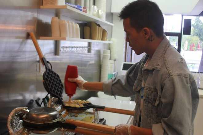 Van Liu works the waffle maker. Each batch of batter is made fresh every morning. - PHOTO BY SARAH FENSKE