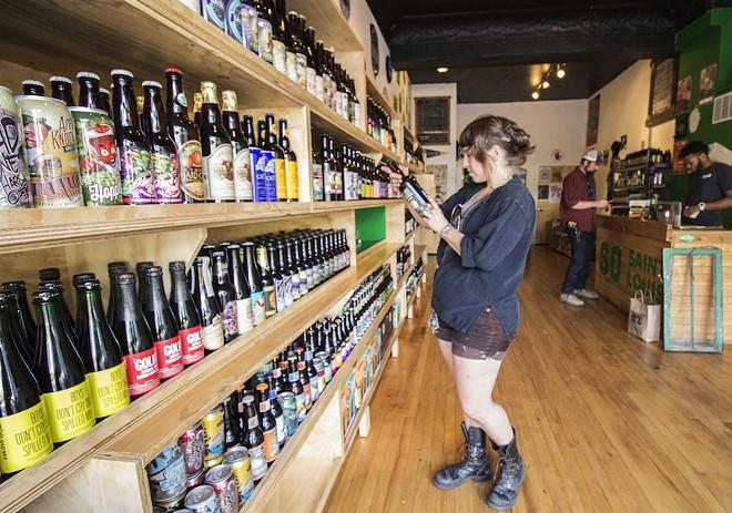Nicole Casper browses the selection at Saint Louis Hop Shop. - PHOTO BY MABEL SUEN