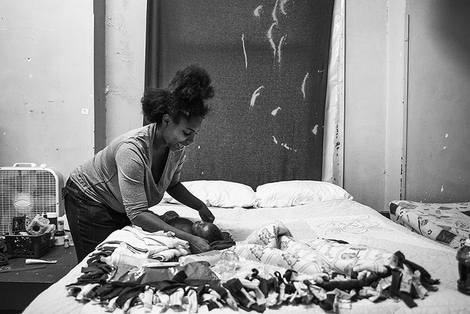 Staci Gill changes her four-month-old son Xavier Gill's diaper in New Life's family shelter. - PHOTO BY NICK SCHNELLE