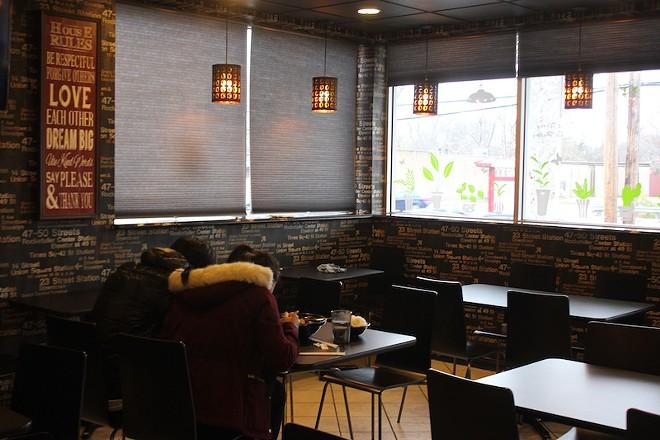 The dark wallpaper gives the space an urban sheen. - PHOTO BY SARAH FENSKE