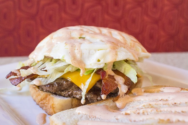 "The ""SLD Burger"" comes with two quarter-pound patties, cheddar, bacon, an over-easy egg, shredded lettuce, red onion and Sriracha ranch on Texas toast. - PHOTO BY MABEL SUEN"