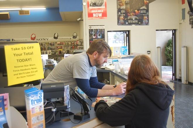 Scott Burk assisting a customer. - PHOTO BY HARLAN MCCARTHY