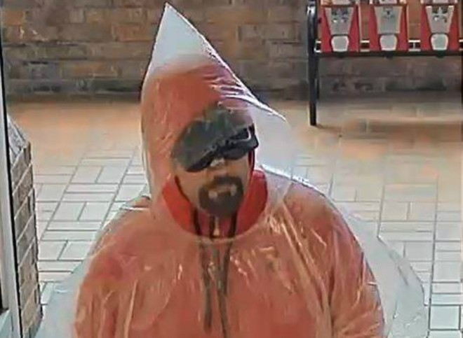 A poncho-wearing robber on Sunday holds up a Collinsville bank. - COURTESY COLLINSVILLE POLICE