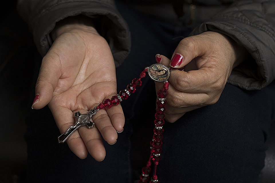 Areli Reyes' mother, Maria, grasps her rosary. - ZIA NIZAMI