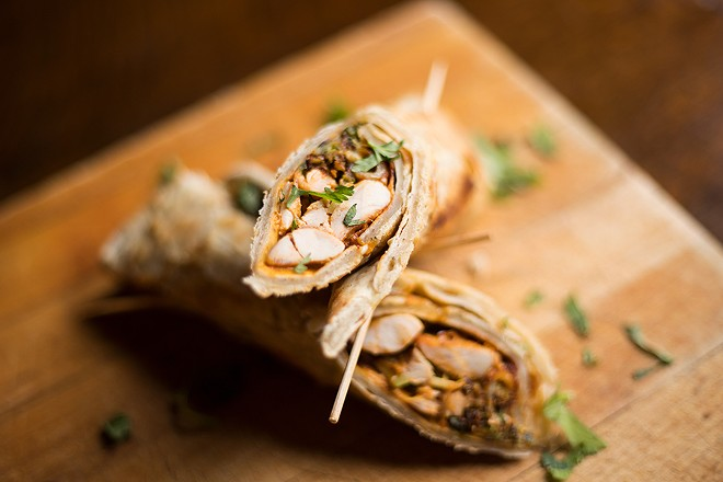 The Chicken wrap stuffs garlic naan with smoked chicken, barbecue sauce, cheese, pickles and sautéed Brussels sprouts. - MABEL SUEN