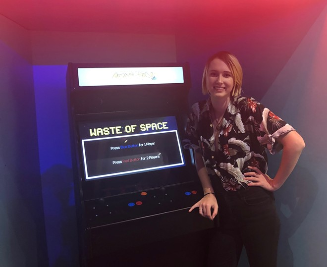 Webster U. graduate Tamsen Reed, next to a game she co-produced for the St. Louis Science Center. - COURTESY OF TAMSEN REED