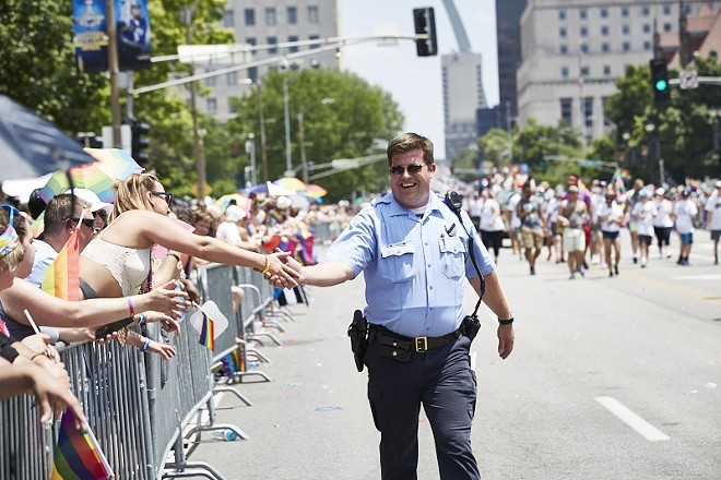 A police officer marches in the 2019 Pride St. Louis parade. - THEO WELLING