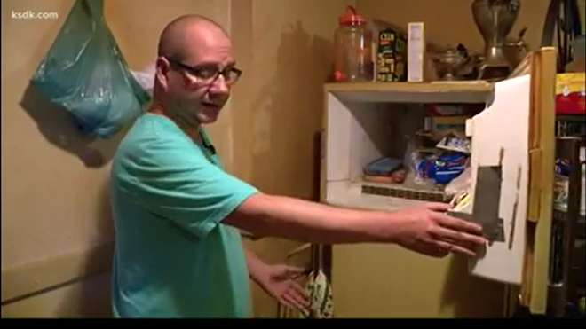 Adam Smith opens the freezer where, he says, a baby's body was kept for decades. - SCREENSHOT/KSDK