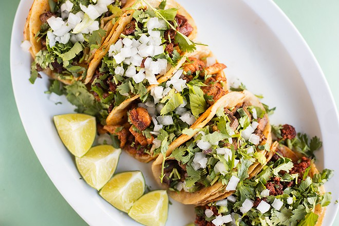 Chorizo, lengua, pollo, cabeza and asada tacos wrapped in corn tortillas are just the first reason to visit Malintzi Mexican Grocery. - MABEL SUEN