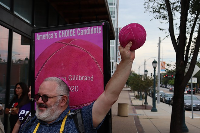 """Marc Daniels holds up pink yarmulkes emblazoned with """"Kirsten Gillibrand 2020."""" - JAMES POLLARD"""
