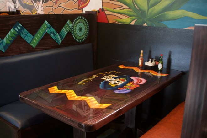 The restaurant logo adorns the booths and tables. - CHERYL BAEHR