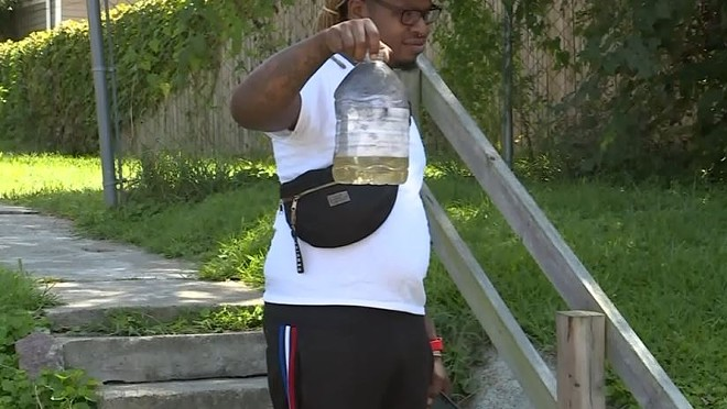 Lamar Conner holds up a bottle of gasoline he says was used in a terrifying home invasion. - SCREENSHOT VIA FOX 2