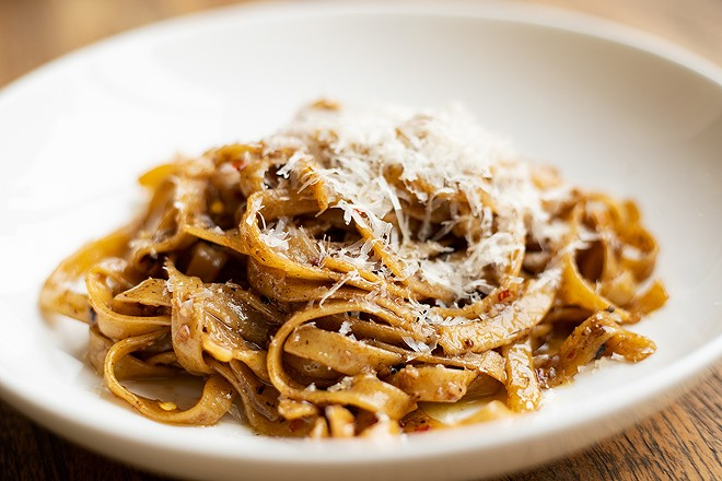 The Grown Up Garlic Noodles combine housemade tagliatelle pasta, olive oil, fermented black garlic, chile flakes and Parmesan. - MABEL SUEN