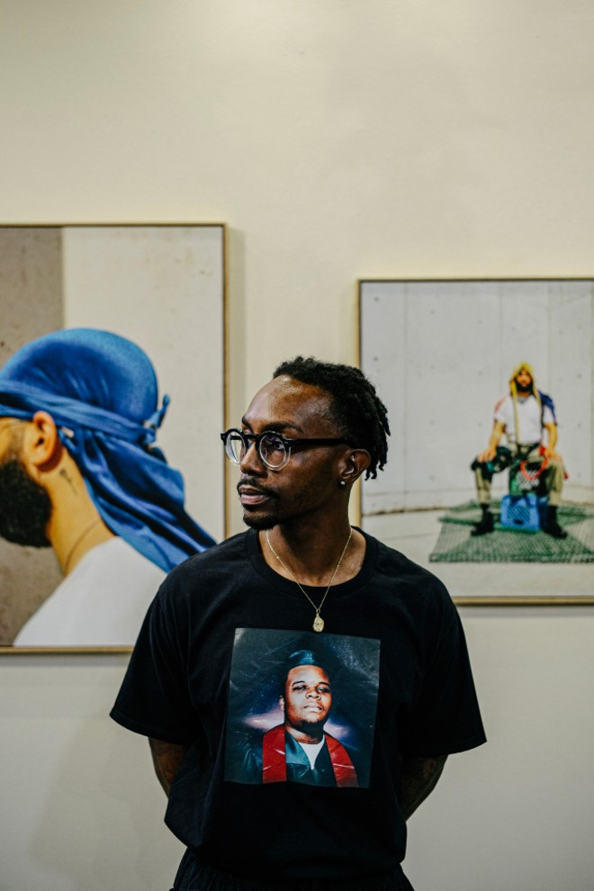Adrian wearing a T-shirt featuring Michael Brown's high school graduated photo taken at The Greens gallery in Columbia, Missouri. - COURTESY ADRIAN WALKER