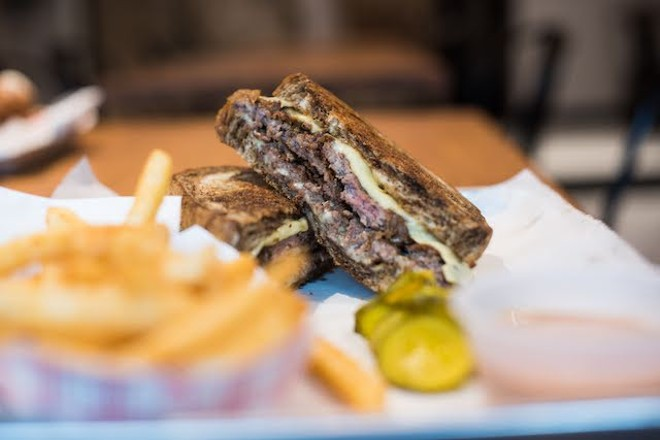 Another view of the pastrami sandwich with a side of fries. - TRENTON ALMGREN-DAVIS