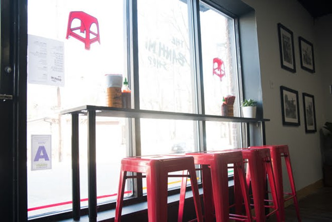 Red stools line the front window at the Bánh Mì Shop. - TRENTON ALMGREN-DAVIS