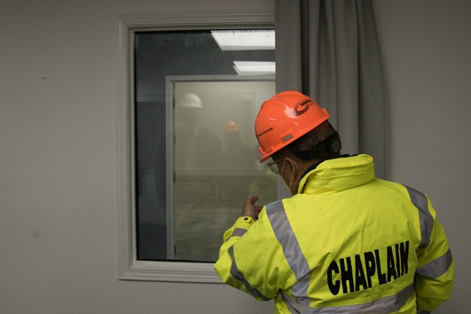 Rabbi Mark L. Shook, Chaplain Coordinator for the St. Louis County Police, points through the visitation window at the Dignity Transfer Center. - TRENTON ALMGREN-DAVIS