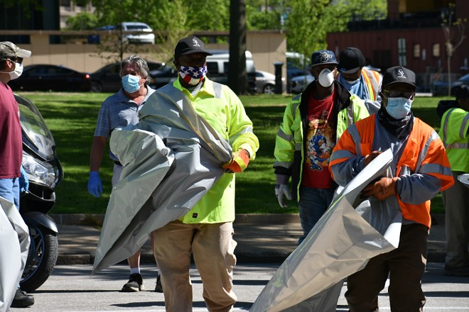City workers with trash bags head into one of the tent cities on Friday. - DOYLE MURPHY