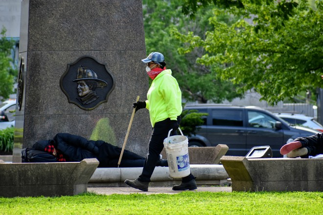 A worker picks up trash after the city removed two tent camps from downtown parks. - DOYLE MURPHY