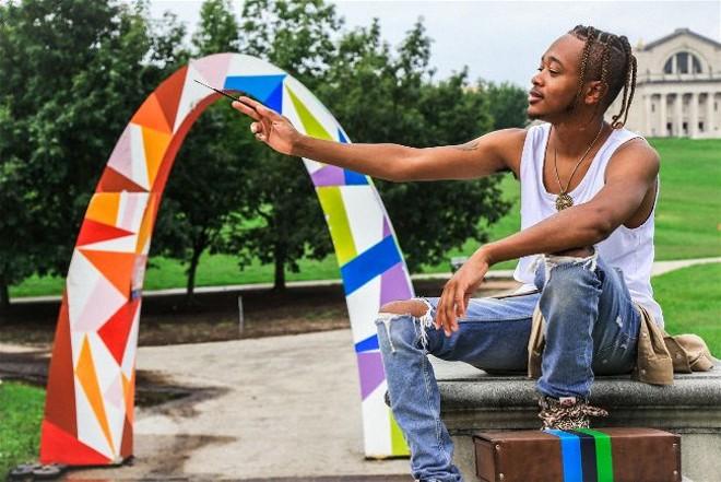 Artist Brock Seals explains the symbolism of the arch he designed. - NICHOLAS COULTER