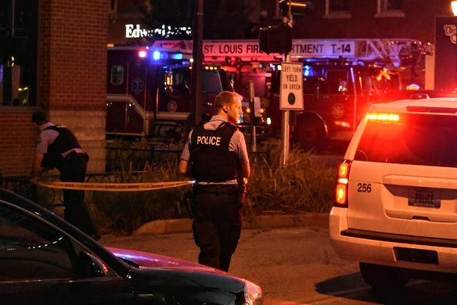 St. Louis police officers stretch crime scene tape across the street after an two officers were shot on Hartford Street. - DOYLE MURPHY