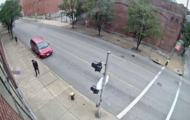 A screen shot shows the suspect in black and a red minivan next to the woman, who is blurred out. - ST. LOUIS POLICE