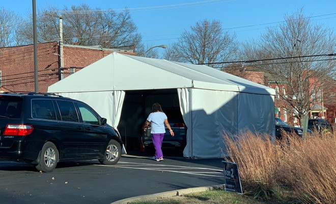 A health-care worker enters a COVID-19 testing tent. - DOYLE MURPHY