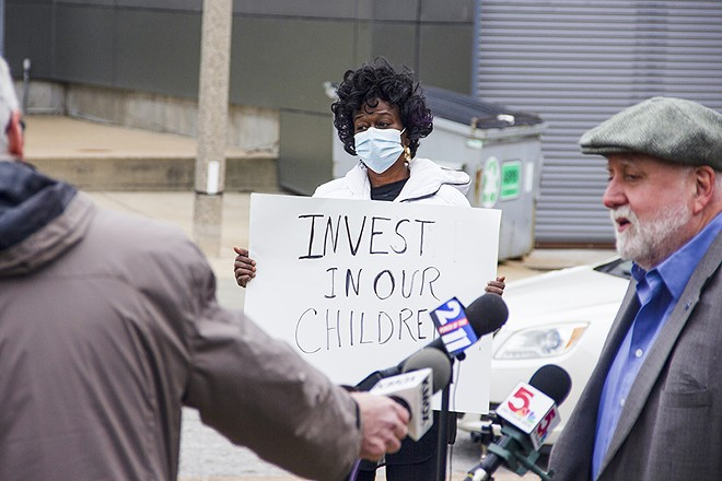 """Gwendolyn Cogshell holds a sign urging school officials to """"Invest in our children"""" during a teacher's union press conference opposing school closings on December 15. - DANNY WICENTOWSKI"""