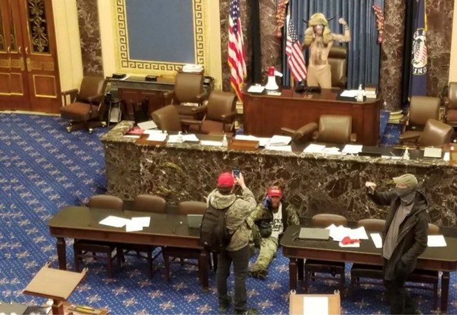 "An evidence photo shows Jacob Chansley, the ""QAnon Shaman,"" on the Senate dais on January 6. - DOJ"