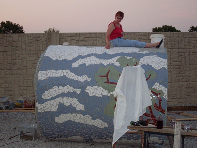 Jeanne Spezia, shown sitting atop the pipe as she covered its concrete surface with tiles. - JEANNE SPEZIA