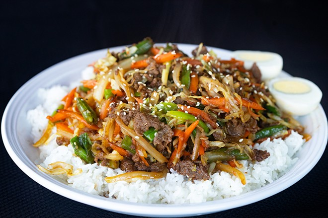Bulgogi beef bowl with marinated beef, onion, carrot, scallion, green bean and cabbage, served over steamed rice with a boiled egg. - MABEL SUEN