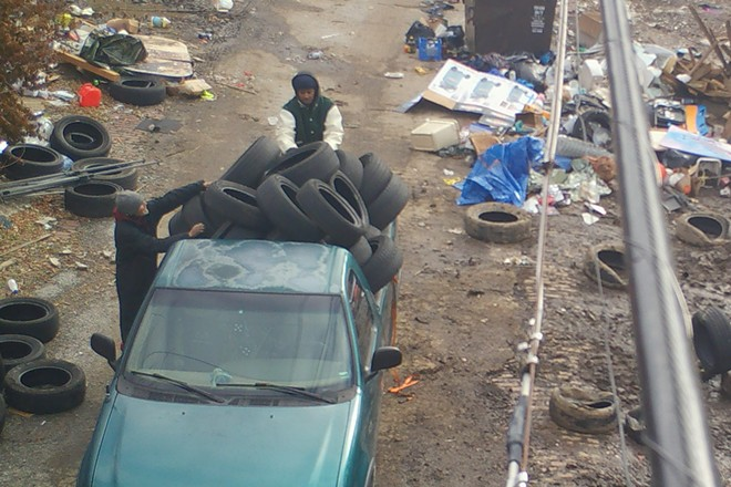 Caught on police camera in February, a two-person team of trash dumpers unloads tires into an alley. - SLMPD