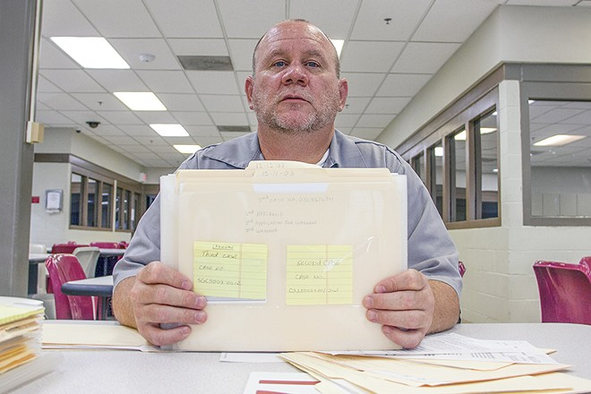 Timothy Prosser, shown here in 2016 with a collection of his legal files, is the only prisoner in Missouri serving a life sentence for drug charges. - DANNY WICENTOWSKI