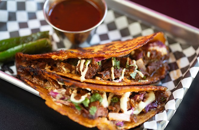 Birria tacos with housemade seitan marinated in vegan consomme, topped with sour cream, red cabbage, diced onions, cilantro and grilled jalapeños in corn tortillas. - MABEL SUEN