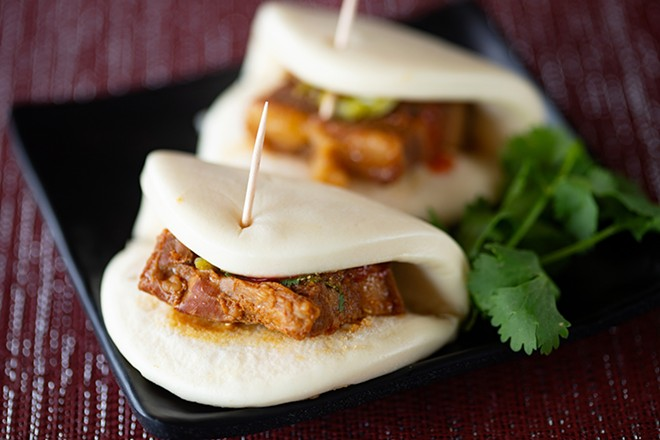 Gua bao (pork belly bun) is a Taiwanese street snack with a steamed bun, braised pork belly, cilantro, ground peanut, pickled mustard green and house sauce. - MABEL SUEN