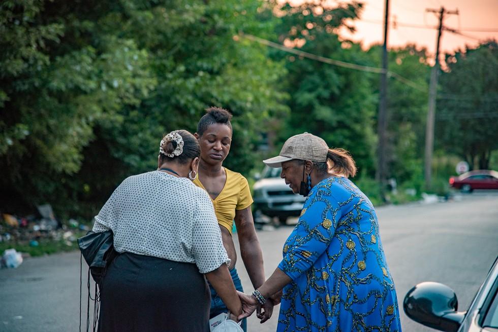 From Left: Pastor Pam, Shameeka Brown and Elder Kenna Sykes-Harper pray together. - ERIN MCAFEE