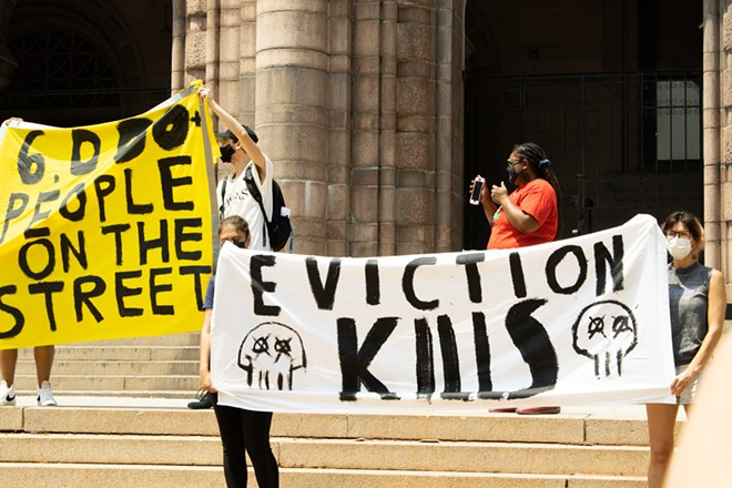 Protesters hold up banners outside City Hall on August 2, 2021. - JENNA JONES